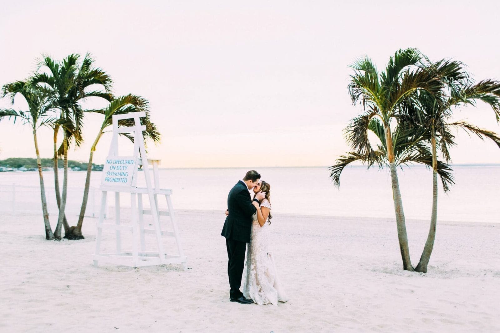 Bride and groom kissing in between two groups of palm trees on the beach of the Crescent Beach Club with water views