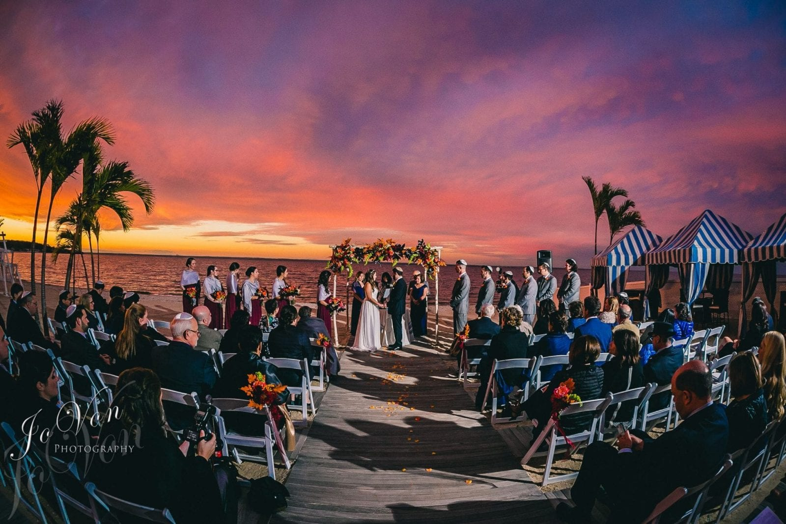 Wedding ceremony in progress on the beach of the Crescent Beach Club as the sun sets over the water