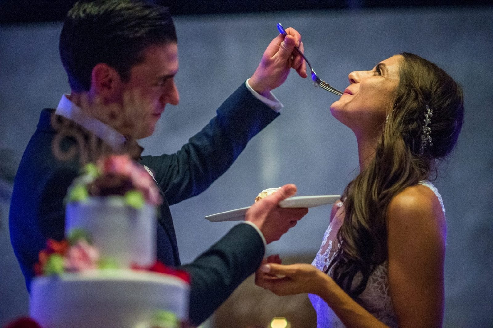 Groom feeding bride cake with a fork in the ballroom of the crescent beach club