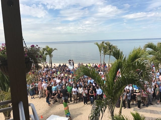 employees gathered on beach for photo at corporate event hosted by the Crescent Beach Club