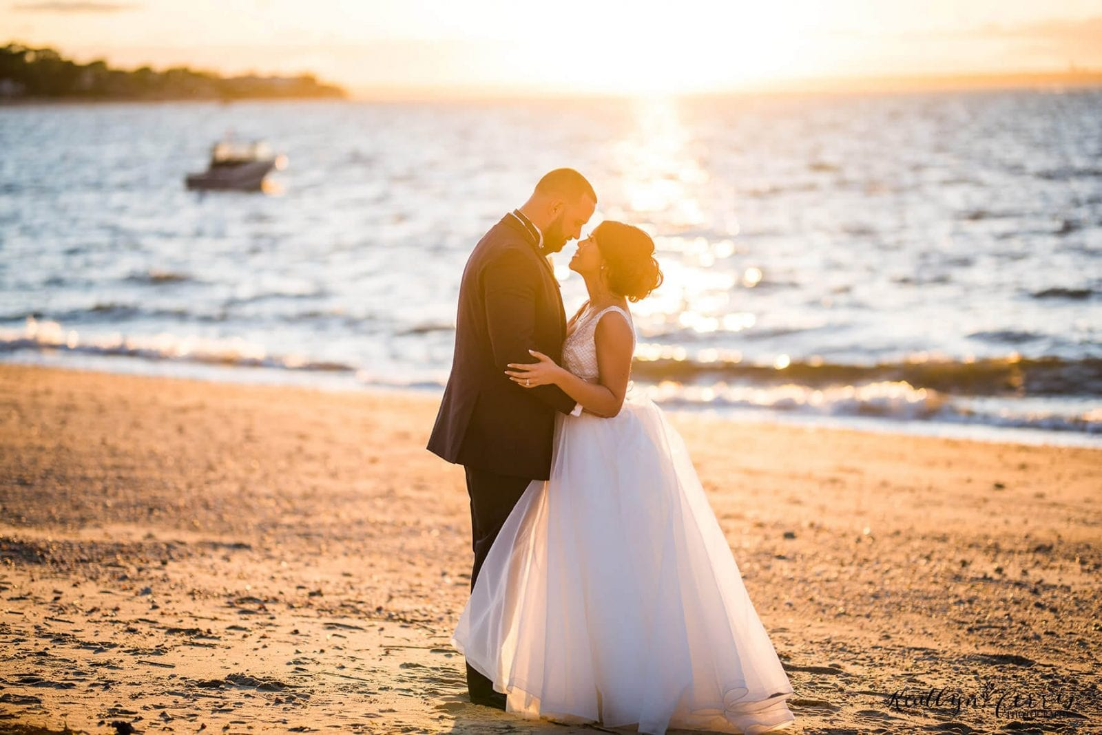 Bride and groom looking into each others eyes on the beach of The Crescent Beach Club in front of the water at sunset