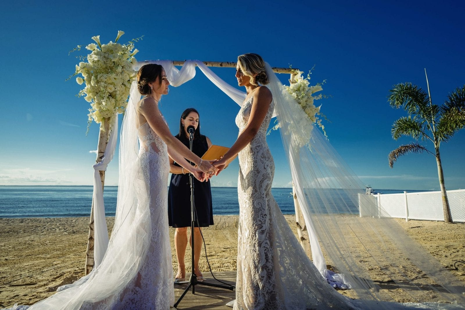 Two brides holding hands and looking at each other during wedding ceremony on the beac of The Crescent Beach Club in front of the water