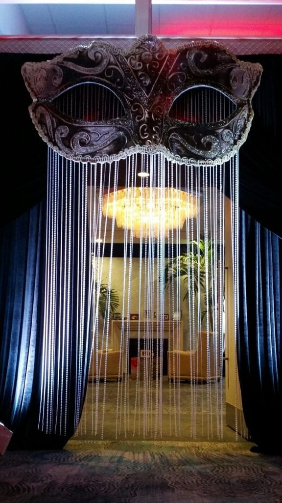 Giant mascaraed mask with long hanging pearl tassels covering a doorway inside the Crescent Beach Club