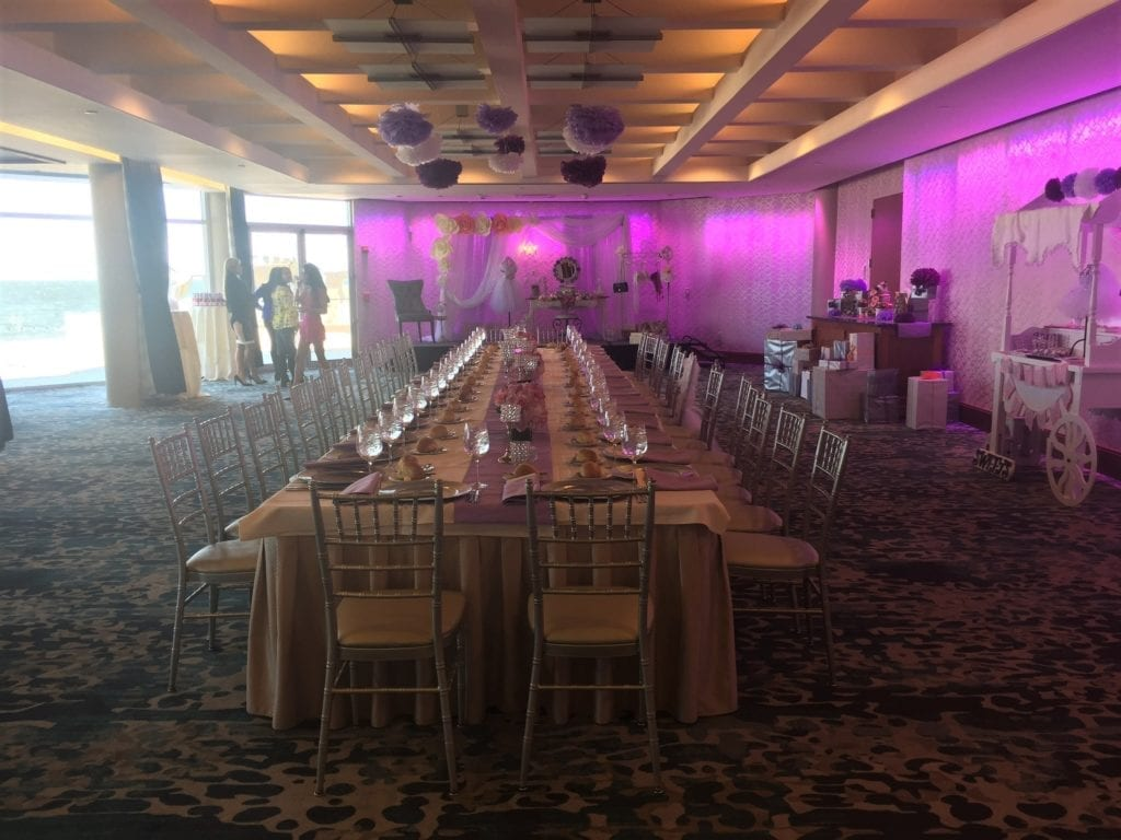 A long rectangle table set up in a pink lit ballroom for a mIlestone event at The Crescent Beach Club