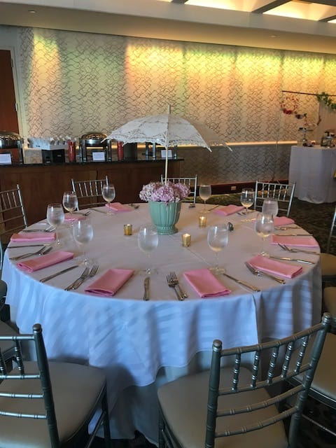 Round table and chairs set up in the Ballroom of the Crescent Beach Club with pink napkins and a pink flower centerpiece with a small lace umbrella sticking out of it