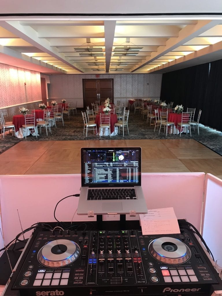 The back of the DJ booth with DJ equipment overlooking a small ballroom at the Crescent Beach Club