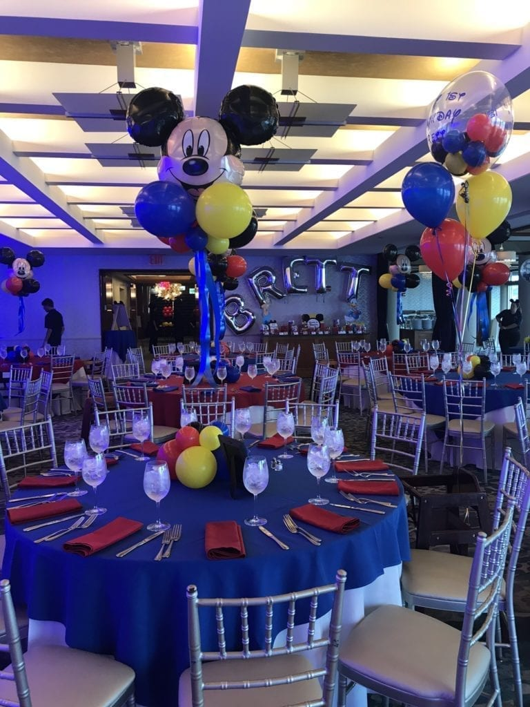 Round Tables and chairs in The Crescent Beach Club ballroom set up with Mickey Mouse themed ballon centerpieces for a Milestone event