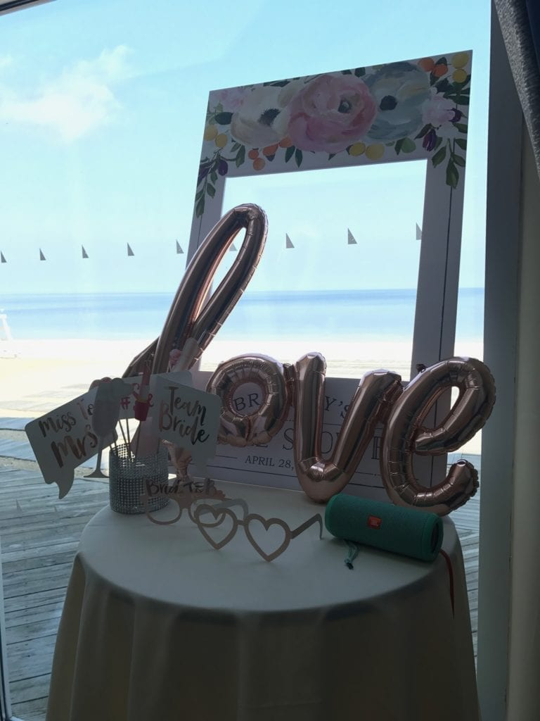 light pink balloons spelling love and picture accessories displayed on a small table with the Crescent Beach Club beach view in the background