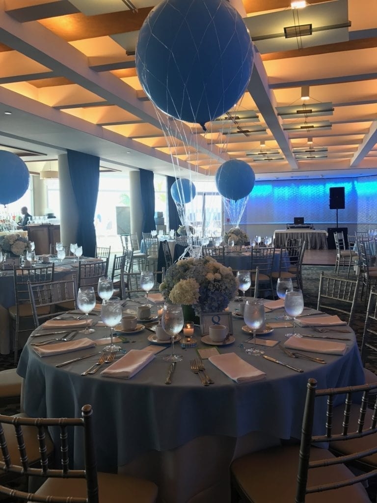 Crescent Beach Club ballroom decorated with blue round tables and Blue netted balloon centerpieces