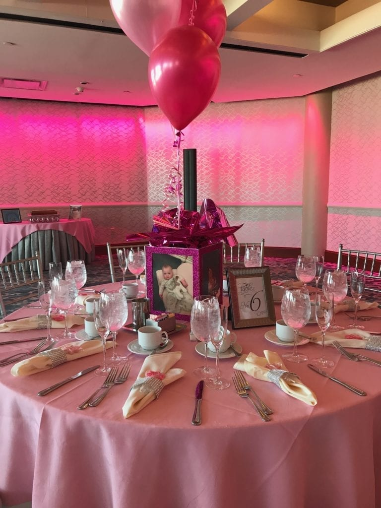 Round table and chairs set up with all pink cloth and balloon centerpiece for milestone event at The Crescent Beach Club