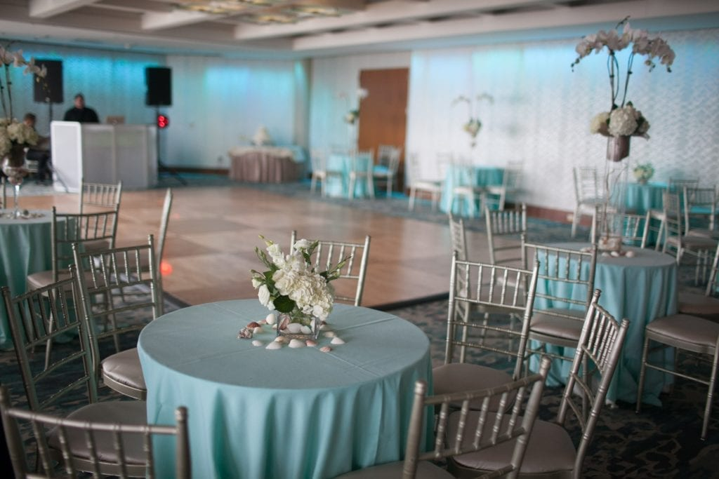 cocktail tables and chairs with flower and shell centerpieces set up in the ballroom of the Crescent Beach Club with DJ in the background
