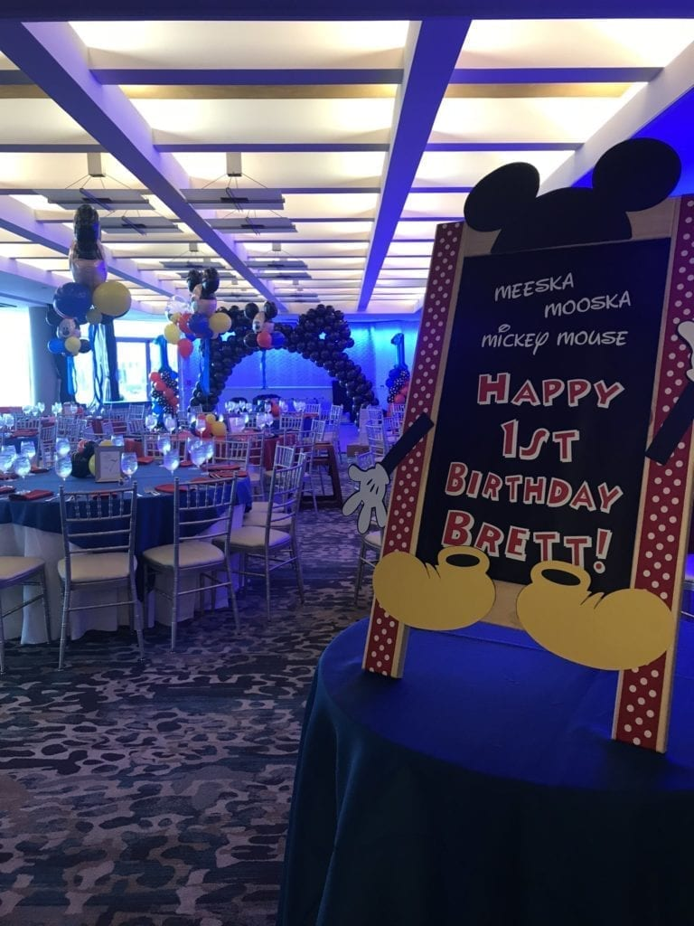 The Crescent Beach Club ballroom decorated in Mickey Mouse theme and sign for a 1st birthday event