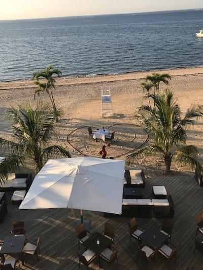 High view of The beach at the Crescent Beach Club with a giant heart outline and intimate dinner for two set up on the sand overlooking the water