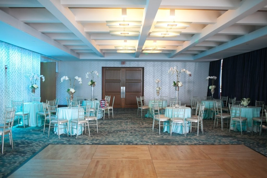 small ballroom at The Crescent Beach Club set up with small cocktail tables and chairs with tall flower centerpieces