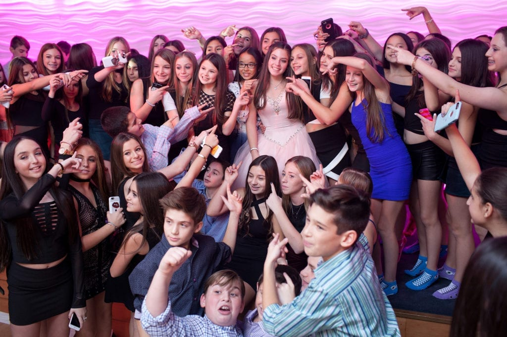 Bat mitzvah girl surrounded by crowd of friends pointing at her in the ballroom of The Crescent Beach Club