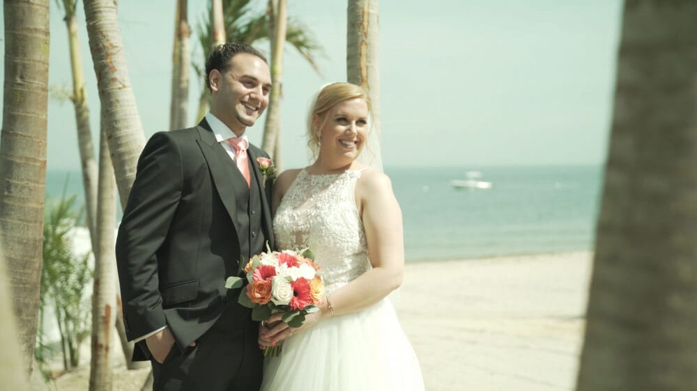 Bride and Groom smiling for a picture off in the distance in front of palm trees on the beach of The Crescent Beach Club