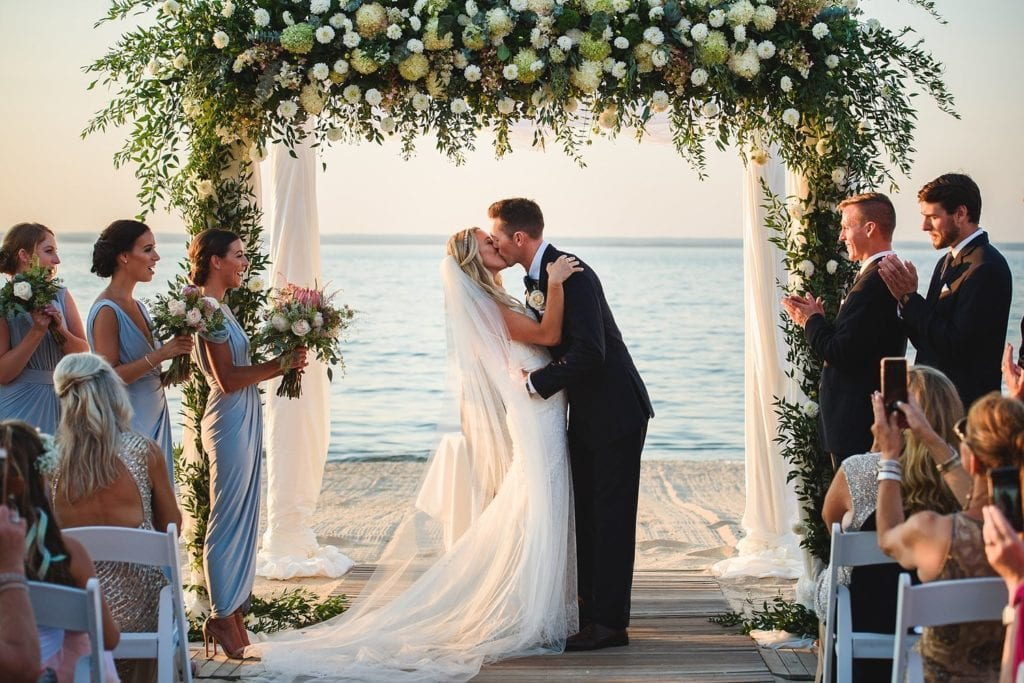 Bride and groom kissing under a canopy of flowers on the beach of the Crescent Beach Club during the ceremony in front of the water view
