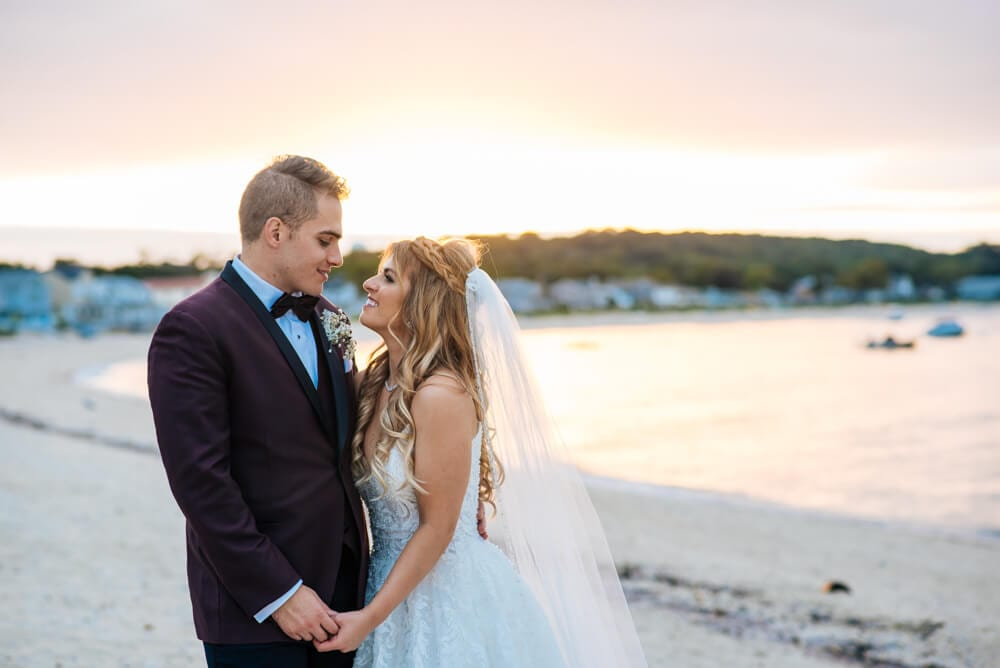 Bride and groom looking into each others eyes and holding hands on the beach of The Crescent Beach Club with water view