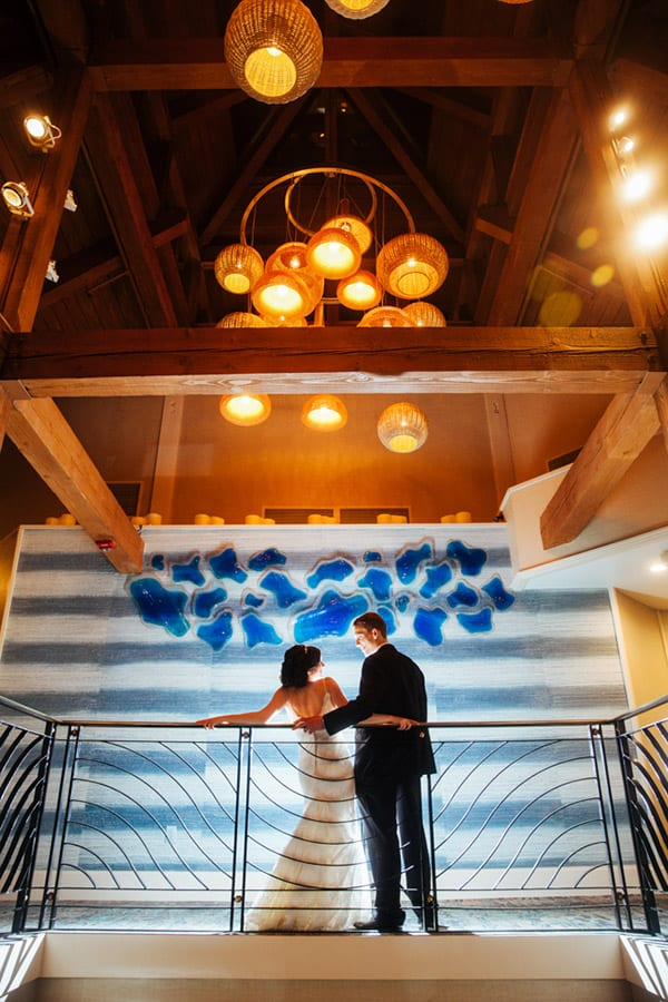 Back of bride and groom against the railing at the top of the staircase under accent chandelier inside the Crescent Beach Club