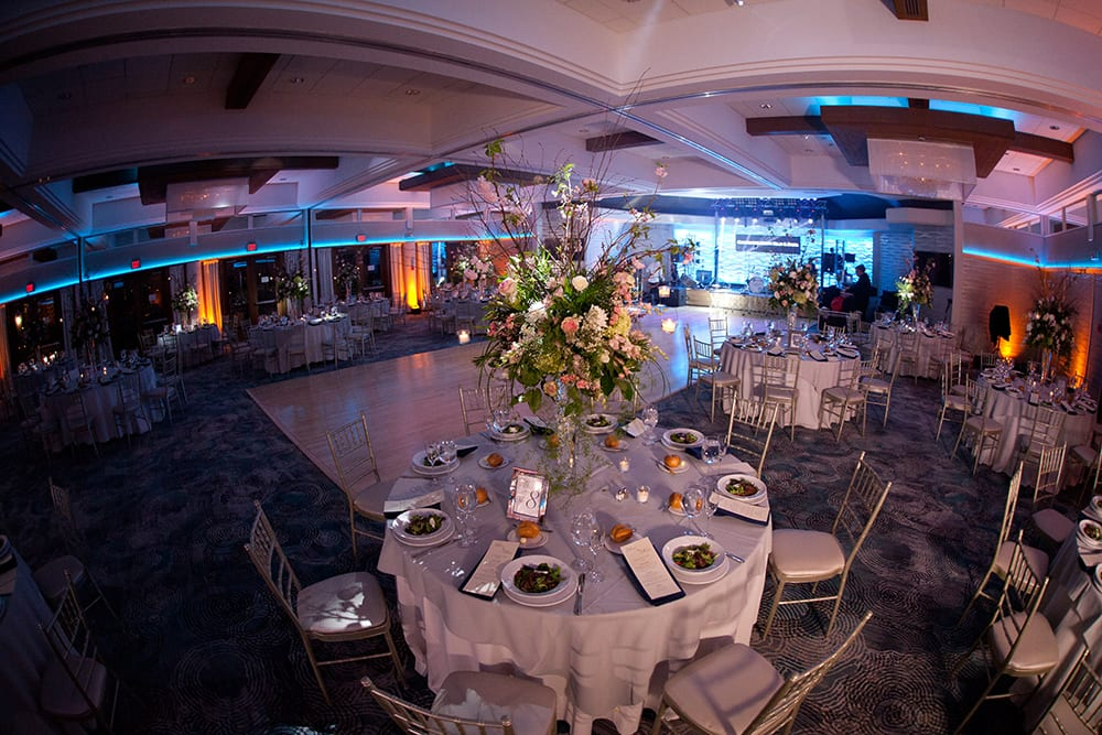 panned out view of The Crescent Beach Club ballroom with tables and chairs and big flower centerpieces