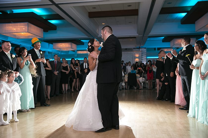Bride and Groom slow dancing in the ballroom of the Crescent Beach Club surrounded by people watching