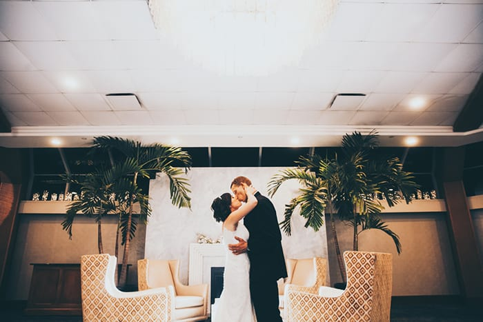 Bride and groom kissing in front of the fireplace inside the Crescent Beach Club