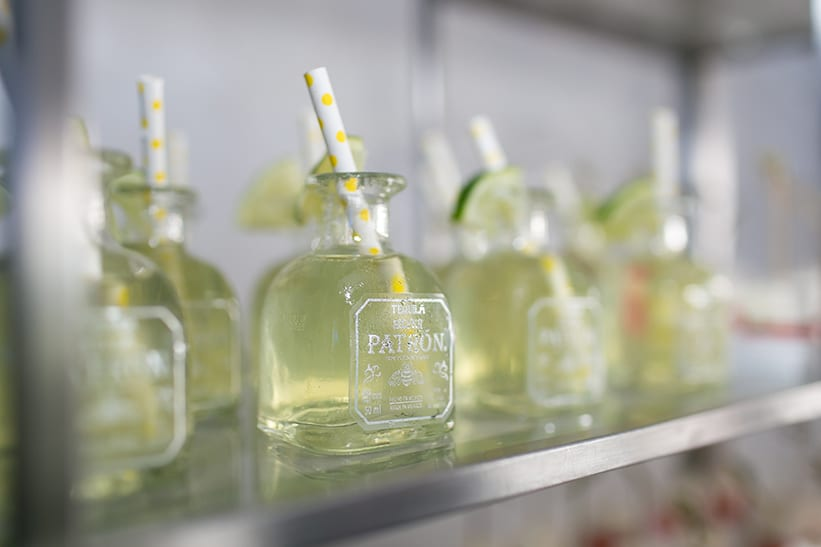 patron bottle with lime individual drinks on a shelf