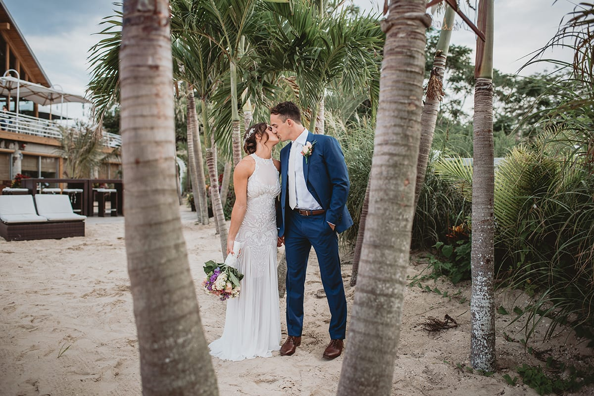 Bride and groom kissing in between the group of palm trees on the beach of the Crescent Beach Club