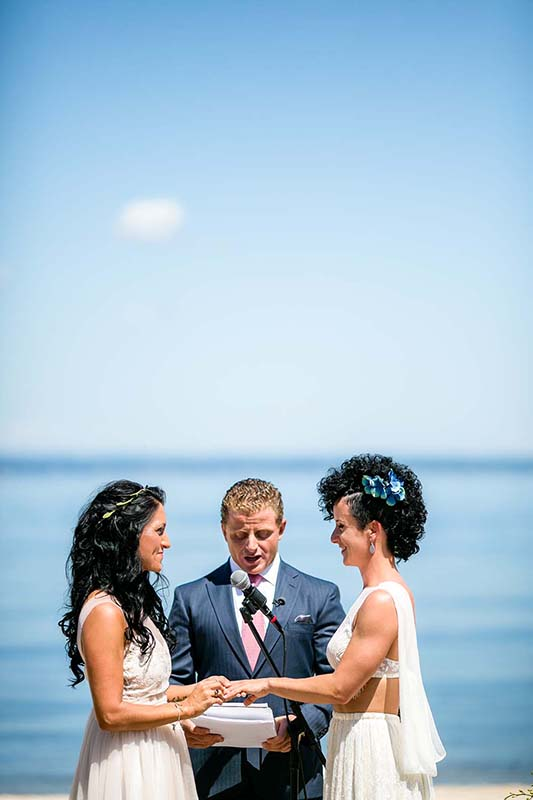 Two brides holding hands saying vows during wedding ceremony on the beach of the Crescent Beach Club