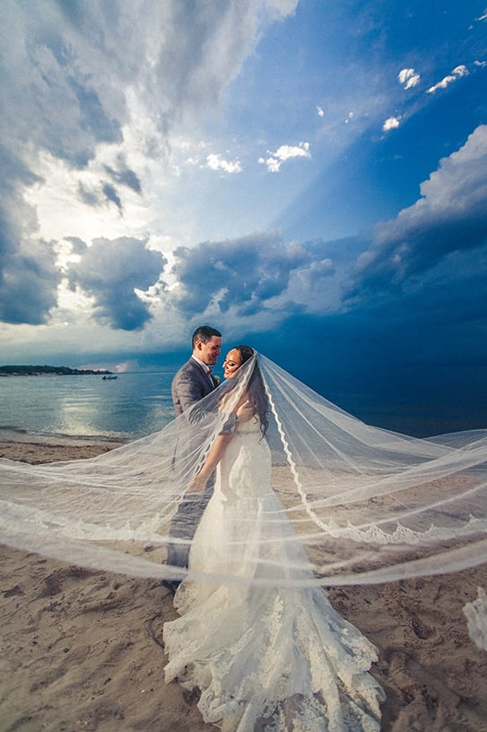 Bride and groom embracing on the beach of the Crescent Beach Club with brides vail expanded across the view