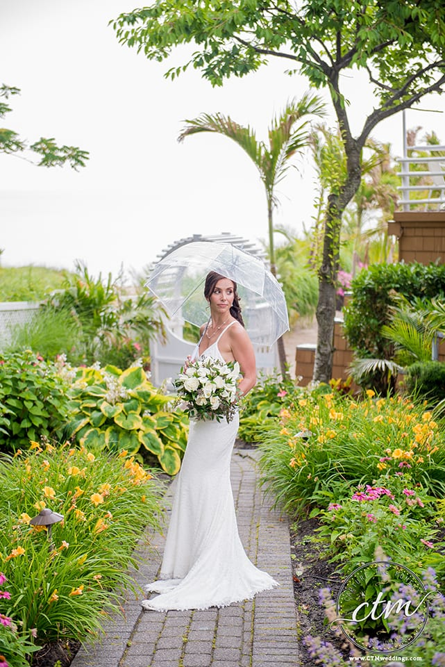 Bride standing on path surrounded by flowers at the Crescent Beach Club holding clear umbrella over her