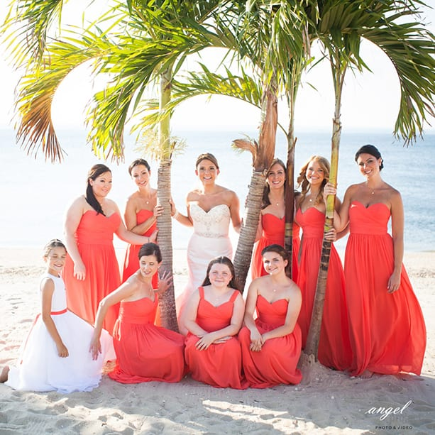 Bride and wedding party posing for picture with palm trees on the beach on the Crescent Beach Club with view of water in the background