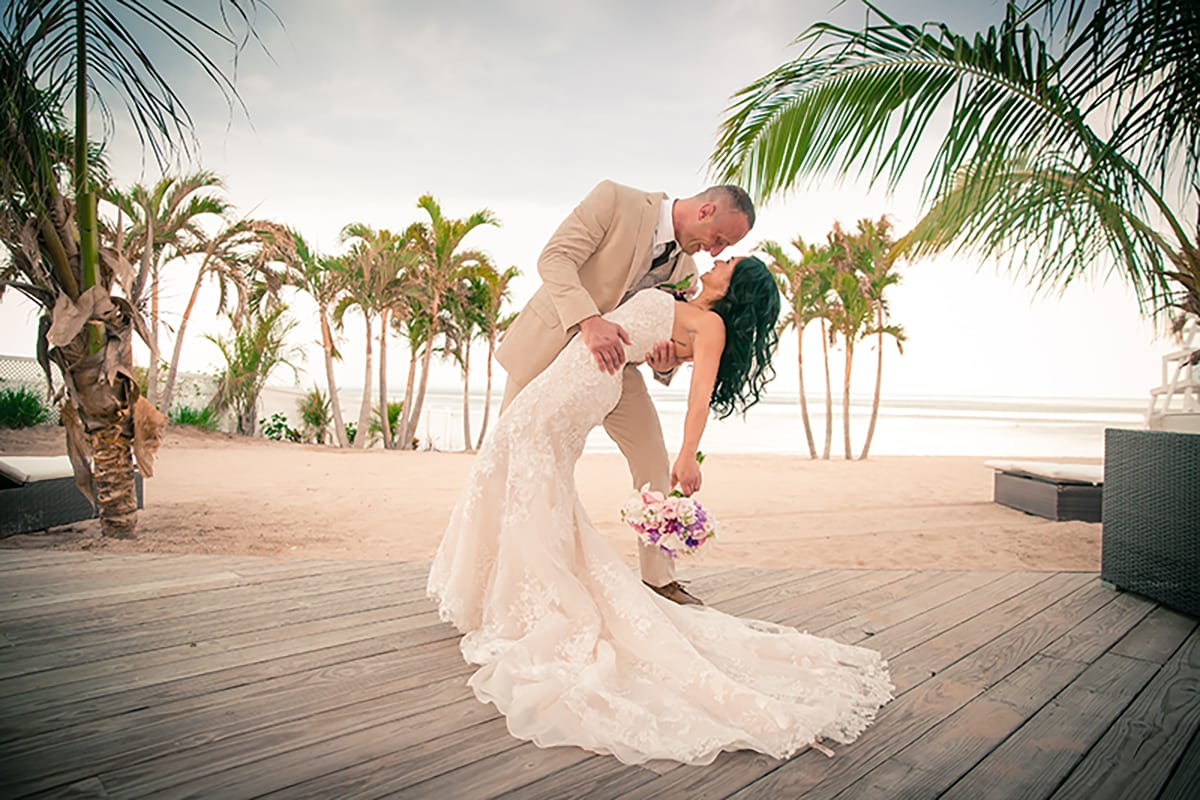 groom dipping bride on the back deck of the crescent beach club overlooking palm trees and water background