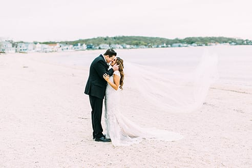 Bride and groom kissing on the beach of the Crescent Beach Club with brides vail blowing behind her